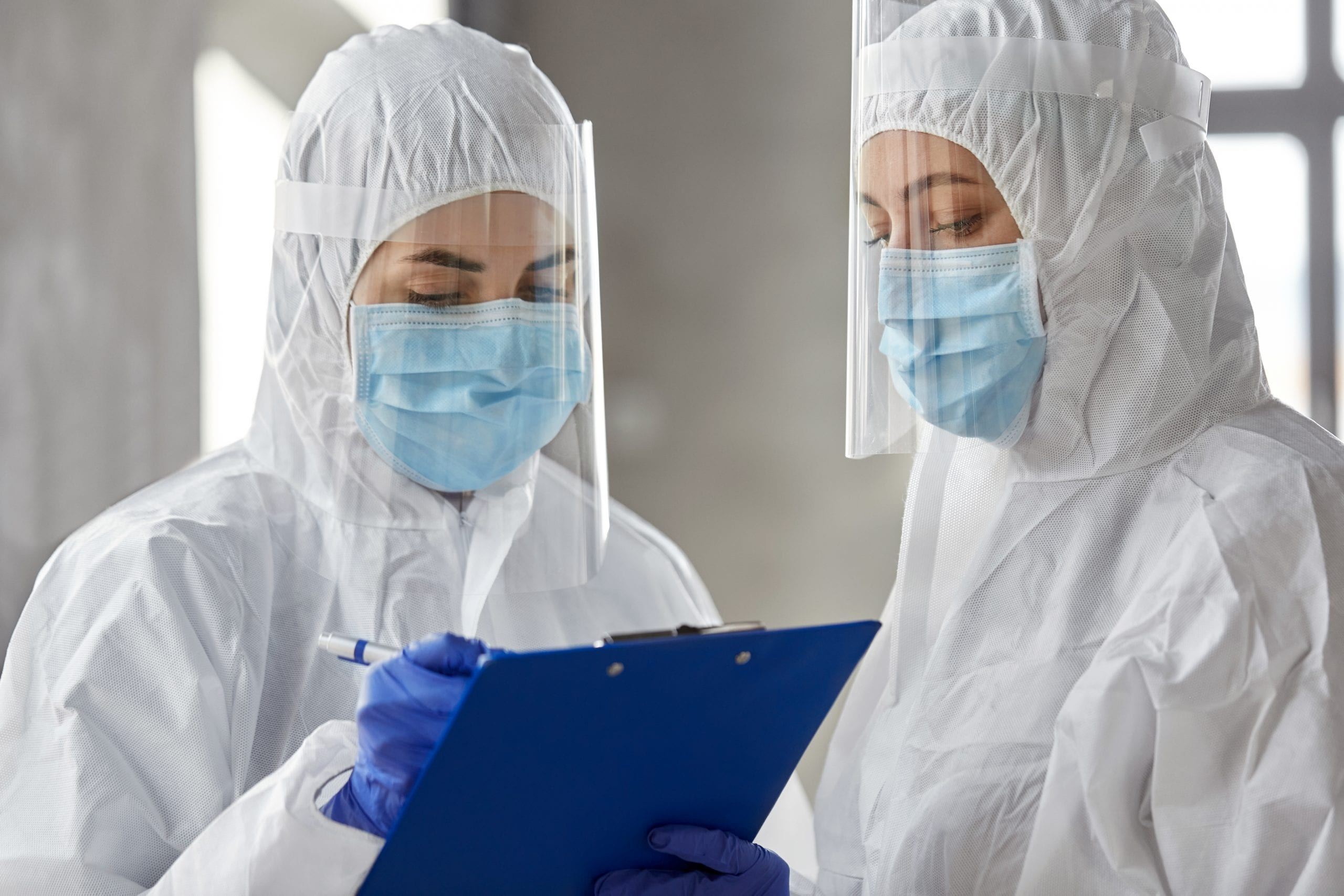 health safety, medicine and pandemic concept - female doctors or scientists in protective wear, medical masks, gloves and face shields for protection from virus disease with clipboard